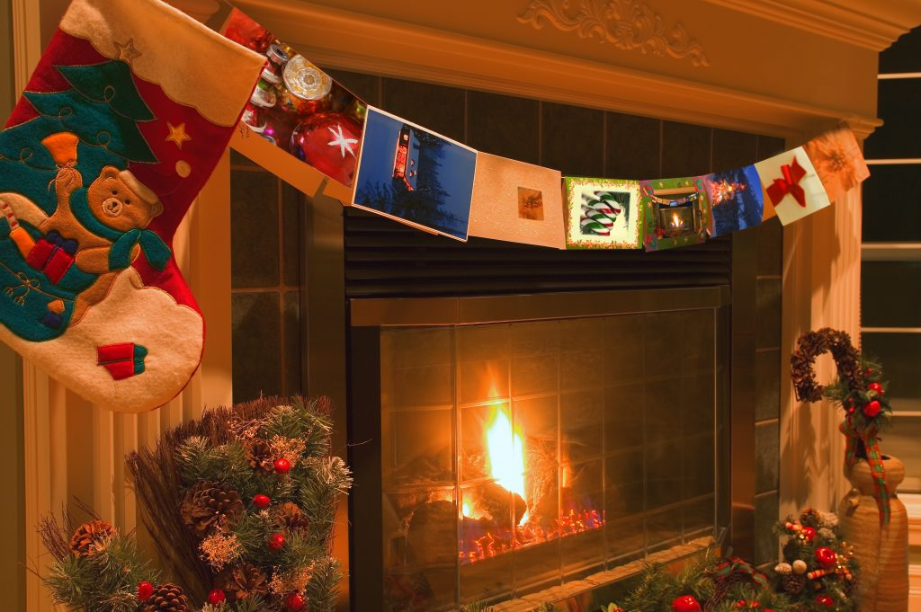 A warm family hearth with a cozy fire and a string of Christmas cards handing on the mantle.
